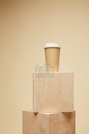 disposable coffee cup on wooden cubes isolated on beige