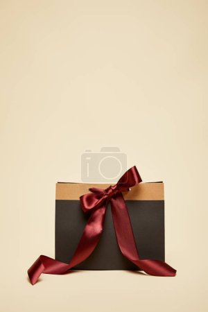 fashionable black shopping bag with burgundy bow isolated on beige