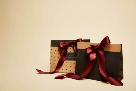 paper brown and black shopping bags with bows isolated on beige