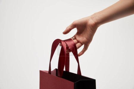 cropped image of woman holding red shopping bag in hand isolated on white