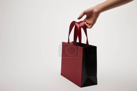 cropped image of girl holding burgundy shopping bag isolated on white