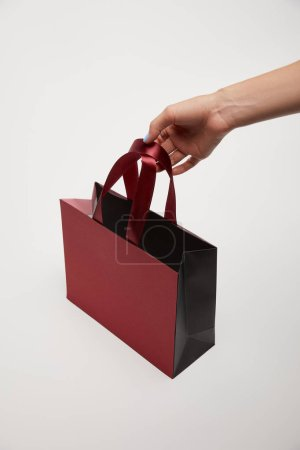 cropped image of girl holding burgundy shopping bag in hand isolated on white