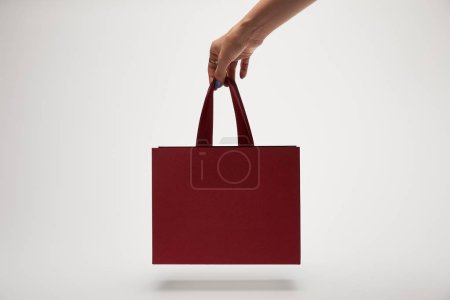Photo for Cropped image of woman holding burgundy shopping bag in hand isolated on white - Royalty Free Image