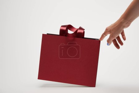 cropped image of woman touching burgundy shopping bag isolated on white