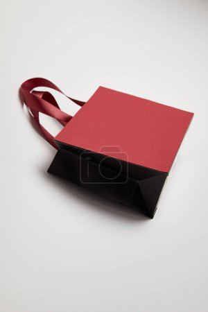 one burgundy shopping bag on white surface