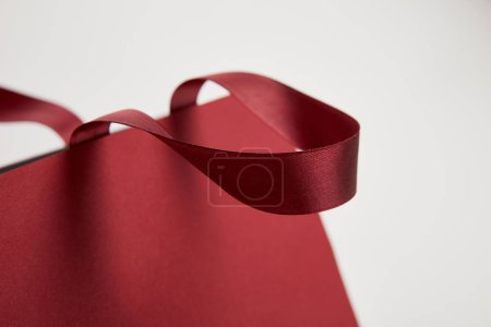 close up of handle of burgundy shopping bag isolated on white