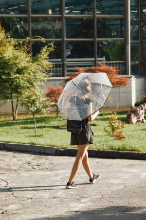 rear view of woman walking with transparent umbrella in summer park