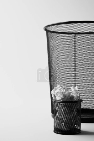 close-up shot of big and small office trash bins with crumpled papers on white