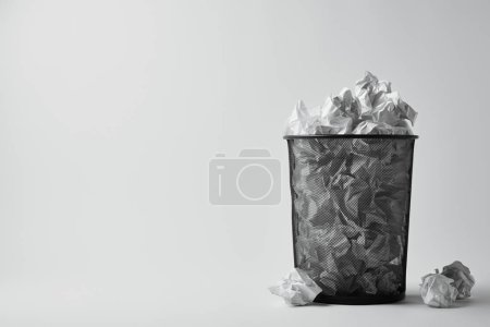 office trash bin with crumpled papers on white surface