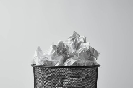close-up shot of office trash bin with crumpled papers isolated on white