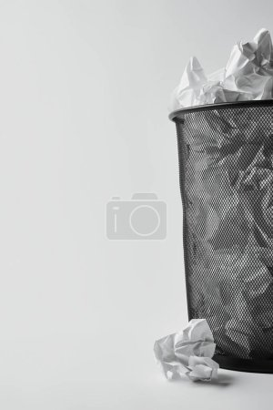 close-up shot of office trash bin with crumpled papers on white