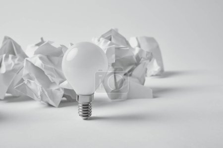 close-up shot of power saving light bulb with crumpled papers on white