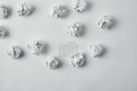 top view of spilled crumpled papers on white surface