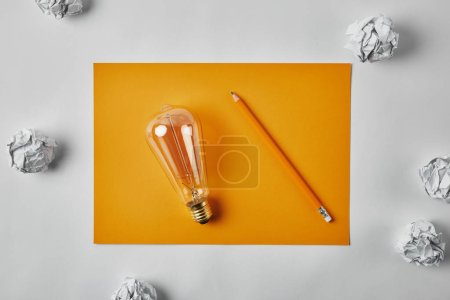 top view of incandescent lamp on blank yellow paper with pencil surrounded with crumpled papers on white surface