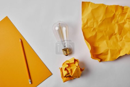 top view of yellow papers with vintage incandescent lamp and pencil on white surface