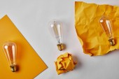 top view of yellow papers with vintage incandescent lamp on white surface