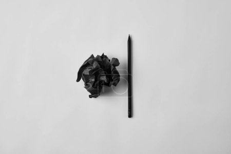 top view of black crumpled paper with pencil on white surface