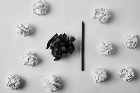Photo for Top view of crumpled black and white papers with pencil on white surface - Royalty Free Image