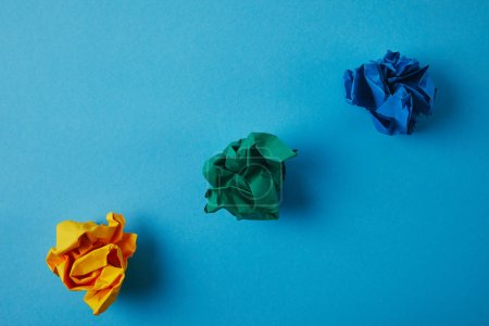 top view of colorful crumpled papers on blue surface