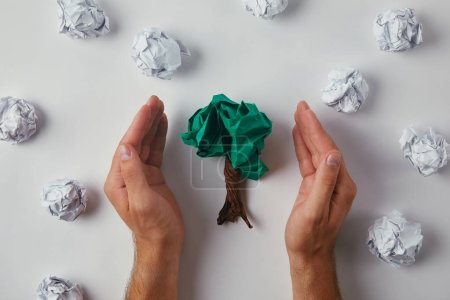cropped shot of man covering crumpled papers in shape of tree on white surface
