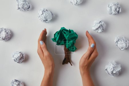 cropped shot of woman covering crumpled papers in shape of tree on white surface