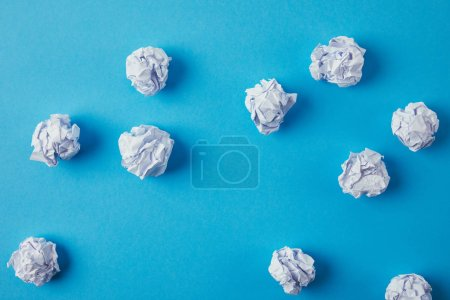 top view of crumpled papers on blue surface