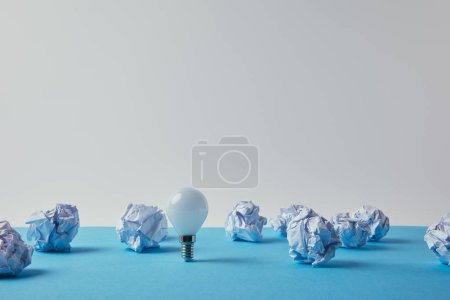 close-up shot of power saving light bulb with crumpled papers on blue surface