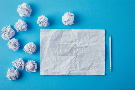 top view of crumpled papers and pencil on blue surface