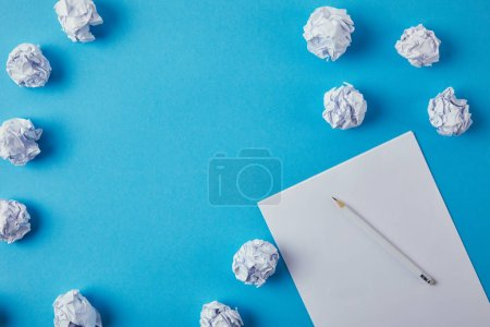 Photo for Top view of crumpled papers with blank paper and pencil on blue surface - Royalty Free Image