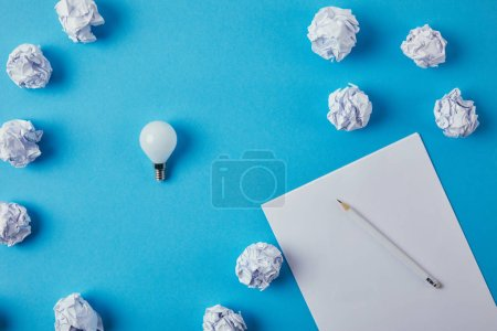 top view of power saving light bulb with crumpled papers on blue surface