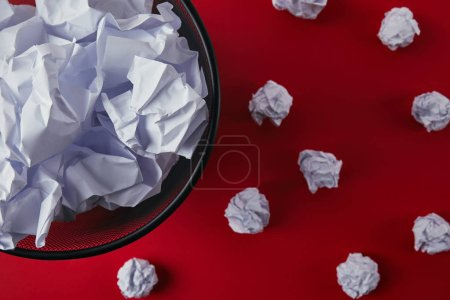 top view of office trash bin with crumpled papers on red tabletop