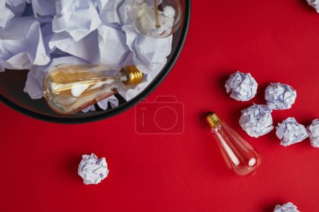 top view of office trash bin with crumpled papers and vintage incandescent lamps on red tabletop