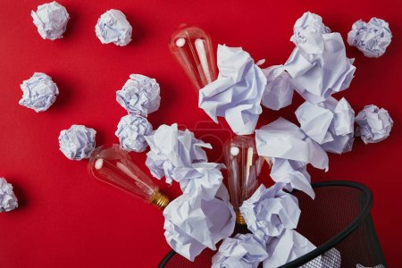 top view of crumpled papers with vintage incandescent lamps spilled from trash bin on red tabletop