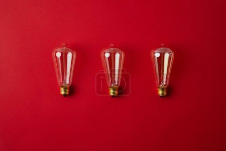 top view of row of vintage incandescent lamps on red tabletop