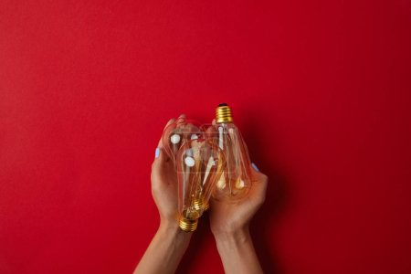 cropped shot of woman holding vintage incandescent lamps on red tabletop