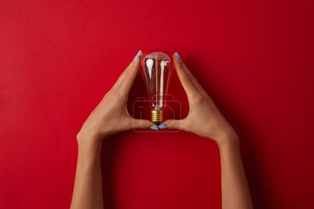 cropped shot of woman holding vintage incandescent lamp on red tabletop