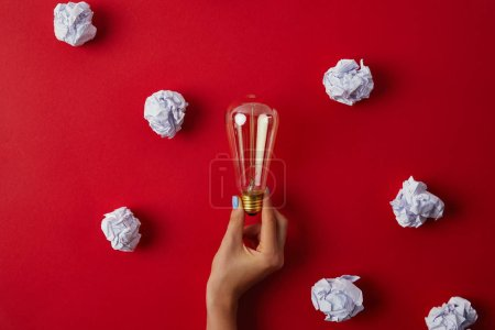 cropped shot of woman holding vintage incandescent lamp surrounded with crumpled papers on red surface