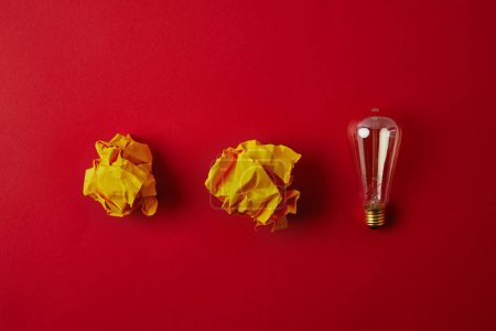 vue de dessus de froissé jaunes papiers avec lampe à incandescence sur la surface rouge