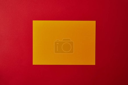 top view of blank yellow paper on red surface