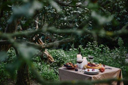 Photo pour Tarte aux baies, vin et bougies sur la table dans le jardin avec des arbres verts - image libre de droit