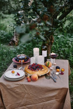 tasty appetizing berries pie, wine and candles on table in garden