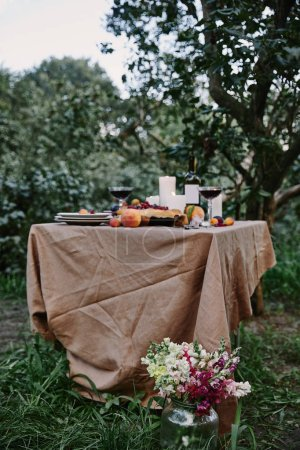 served table in garden, bouquet of flowers on grass