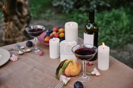 candles and red wine on table in garden