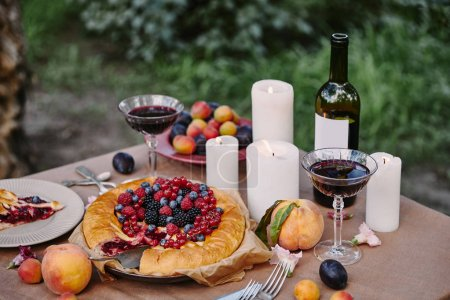 tasty appetizing berries pie and candles on table in garden
