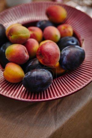 Photo pour Gros plan de délicieuses prunes mûres et les abricots sur plaque sur la table - image libre de droit