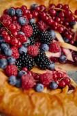 close up of tasty berries pie with raspberries, currants, blueberries and blackberries