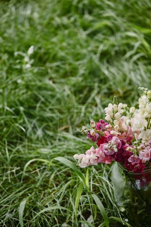 bouquet of flowers in glass jar on green grass