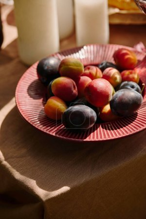 organic plums on plate on table in garden