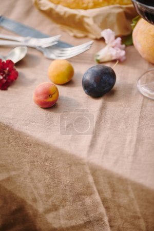 Foto de Ciruelas y utensilios sobre mantel beige en jardín - Imagen libre de derechos