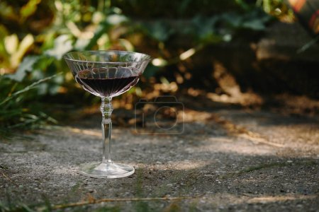 one glass of red wine on road in garden